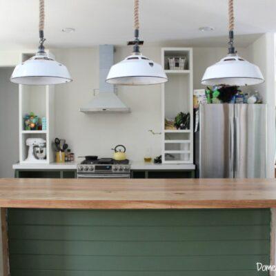 Kitchen Progress – Dark green cabinets, a rustic wood countertop, and lighting